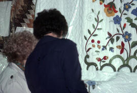 Women looking at quilts before auction