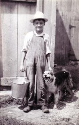 Wilbur J. Shantz and his dog doing chores on the