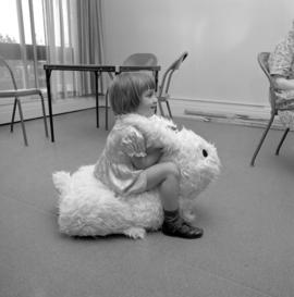 Child playing with a stuffed animal in the craft room at Fairview Mennonite Home