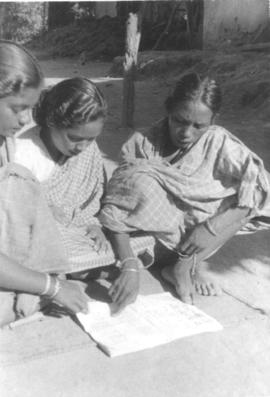 Two Indian women sit on the ground reading from a book