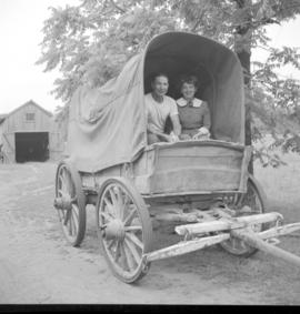 A man and a woman sitting in the back of the Conestoga wagon