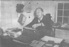 A. A. Wiens working at his desk.
