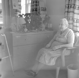 A woman sits in a chair in her room at the United Mennonite Home for the Aged (Vineland, Ontario)