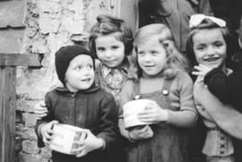 Children (in Vienna?) hold tins of candy given to MCC