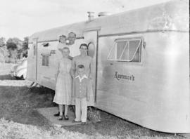 Lawrence Brunk family standing beside their trailer