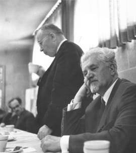 Ivan Motorin sits at the table while Adolph Klaupiks stands