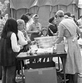 Mennonite women selling items and food at the Relief Sale in New Hamburg, Ontario