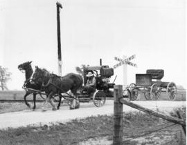 Amish man towing a power engine and his buggy.