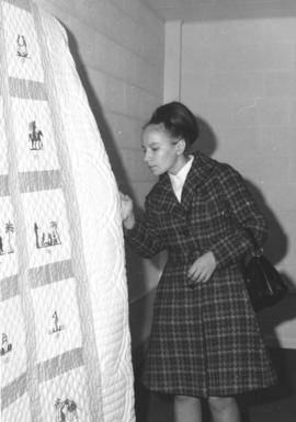 Miss Valentina Ryndina from Moscow inspects the handiwork of an American quilt