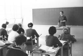 A woman teaching female high school students in a