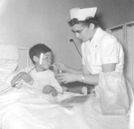 Marie Neufeld feeds a patient at the Clearwater Lake Sanatorium