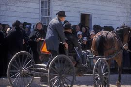 Old Order Mennonites with horse and buggy parked