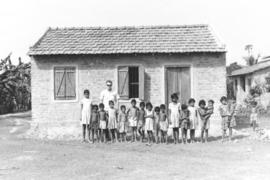 Children are lined up in front of a well kept building with a tile roof