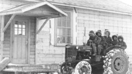 Children on a tractor with one of the men of Mennonite Pioneer Mission