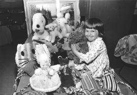 A young girl sits with some of the stuffed toys