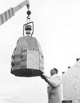A communications satellite on a hoist being