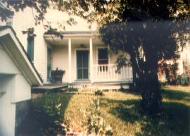 Porch provides entrance to main house on right