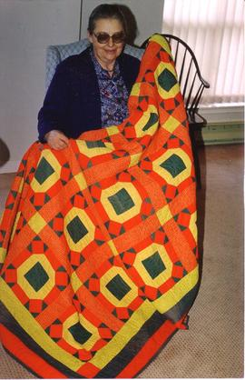 "Lorna Bergey with a ""Rolling Stone"" quilt made"