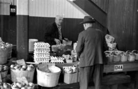 A man selling produce in the upstairs of the old Kitchener Farmer's Market in Kitchener, Ont...