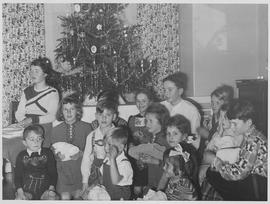 Children of various ages in front of a decorated