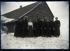 Outdoor group portrait of 15 women standing outside of large building.