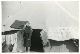 Nurse airing her mattress outside her tent in refugee camp, Egypt.