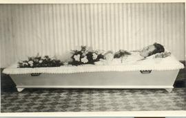 Woman lying in coffin - no lid on coffin