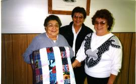 Carrie and sisters with quilt