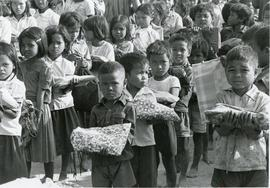 Children in Kampuchea holding school kits