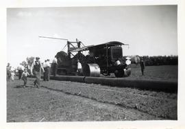 A man and a boy walk alongside a group of men next to a section of pipeline and a piece of machinery