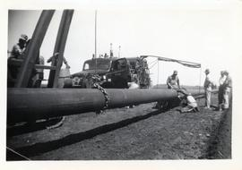 A group of men work to connect two pieces of pipeline by welding