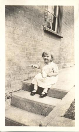 Young gilrl on steps of house