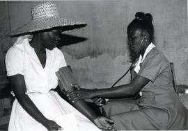 Checking a woman's blood pressure