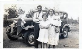 Couple with 2 children in front of a car