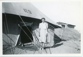Helena Reimer standing outside a tent in Tolumbat camp, Egypt