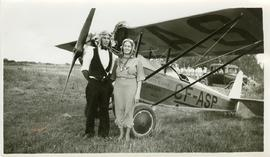 Edwin Friesen and Olga Friesen standing beside airplane
