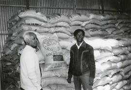 Beyene Mulatu in front of stacked bags of Michigan beans shipped by MCC to Ethiopia