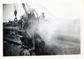 A man uses a piece of machinery to work on the pipeline