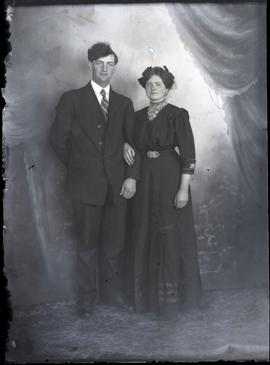 Interior portrait of young, well-dressed couple standing.
