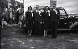 Outdoor, 2 couples in front of a car in front of a building.