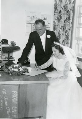 Edith signing the license with Alfred watching her, 1960