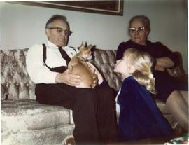 Peter, Mary, little girl and Poncho on a couch