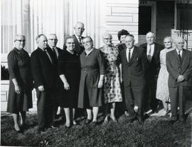 A group of elderly people standing in front of a house