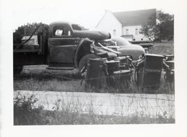 A damaged truck beside a car and a building (church?)