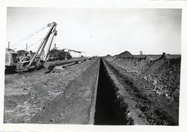 A side boom cat (tractor equipped with lifting boom) and another piece of machinery sit alongside a length of pipeline and a trench