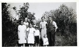 Family group standing in front of bushes, probably in B.C.