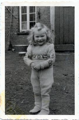 A young girl wearing a knit suit.