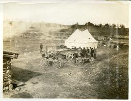 Buggies, wagons and tent in a cleared area