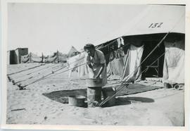 Woman doing laundry outside of a tent in refugee camp, Egypt