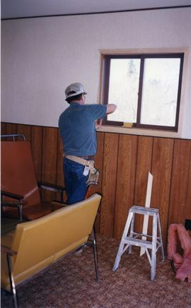 John Zacharias installing windows at Matheson Island